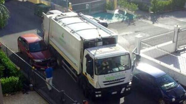 Camion della spazzatura si incastra tra due auto